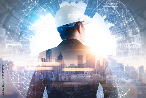 Fotografía  The double exposure image of the engineer standing back during sunrise overlay with cityscape image and futuristic hologram