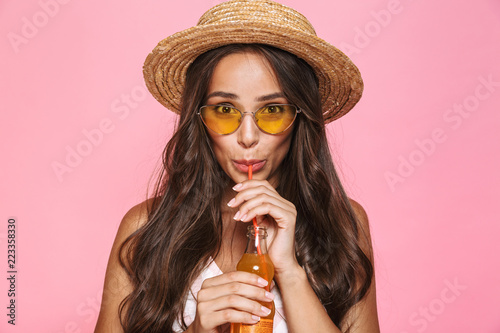 Fotografía  Photo closeup of charming woman 20s wearing sunglasses and straw hat drinking ju