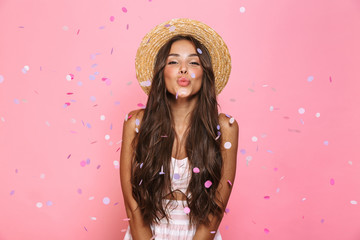 Obraz Photo of beautiful woman 20s wearing straw hat laughing while standing under confetti, isolated over pink background