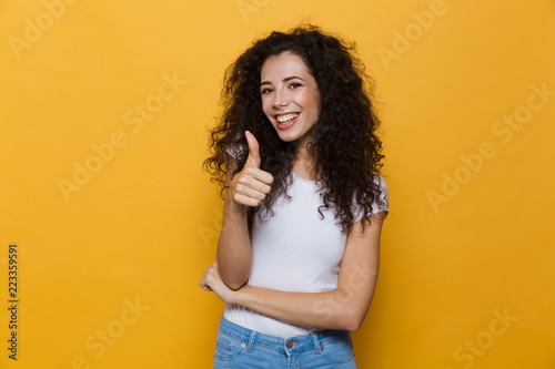 Foto op Canvas Hoogte schaal Image of young woman 20s with curly hair smiling and showing thumb up, isolated over yellow background