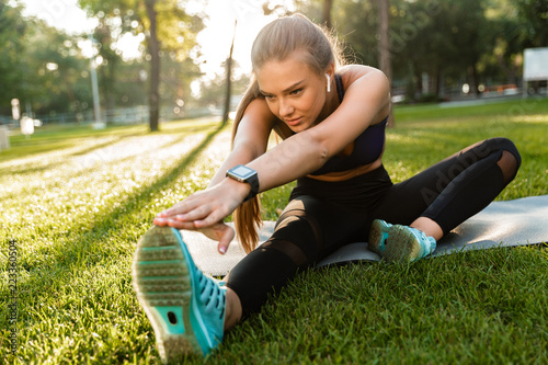 Sports woman in park outdoors make sport stretching exercises.