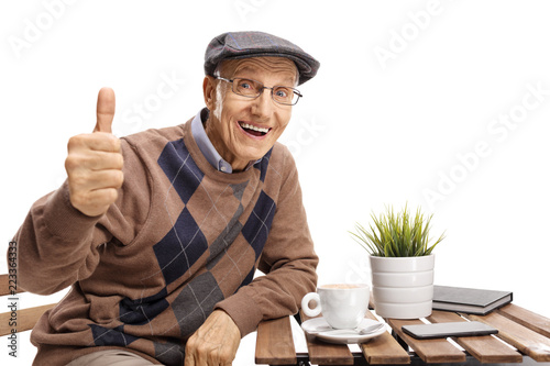 Foto op Canvas Hoogte schaal Senior sitting at a coffee table making a thumb up gesture