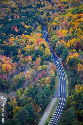 Fotografie, Obraz  A car driving on a road surrounded by fall color in New England - aerial