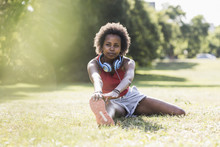 Young Woman Stretching On Meadow In Park