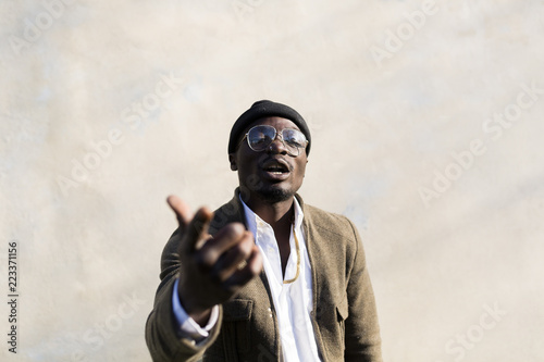 Tuinposter Baksteen muur Young man with woolly hat gesturing in front of wall