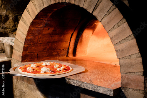 Wall Murals Pizzeria Freshly made pizza being put into hot pizza oven