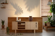 Candles on wooden cupboard and plants in living room interior with shadows on the wall. Real photo