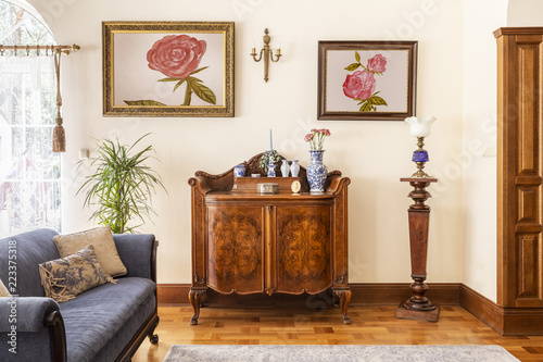 Fototapeta Real photo of an antique cabinet with porcelain decorations, paintings with rose