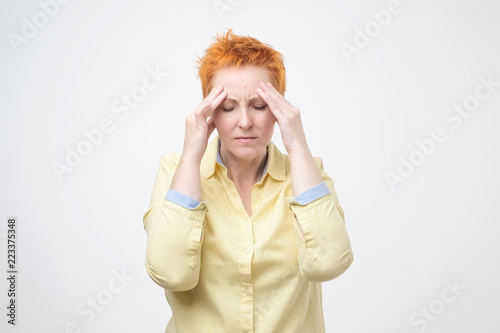 Photo  Exhausted mature woman touching her head with eyes closed