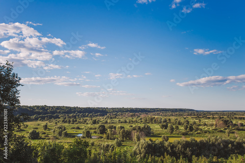 Foto  Beautiful green countryside landscape with charming calm blue sky with fluffy white clouds
