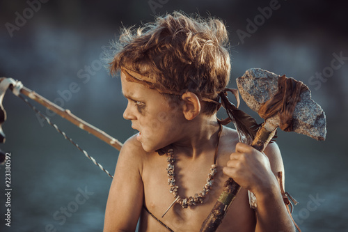 Angry caveman, manly boy with stone axe and bow hunting near river. Prehistoric tribal boy outdoors on nature. Young shaggy and dirty savage, warrior and hunter with weapon. Primitive ice age man in
