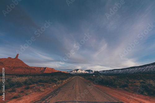 Poster Diepbruine Looking Down A Long Road Running Through A Rock Desert Landscape Of Utah In The Iconic American Southwest