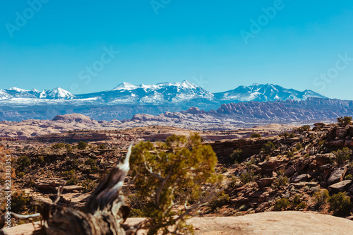 Snow Capped Peaks Over The Red Rock Desert Landscape Of Utah In The Iconic American Southwest