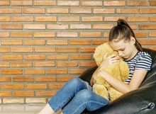 Upset Caucasian Teen Girl Sitting In Black Bean Bag Chair Hug Big Brown Teddy Bear Toy Against Brick Wall. Casual Outfit. Sadeness, Problem Concept