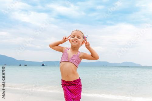 Fotomural Little beautiful girl dressed in swimsuit as a mermaid stay on the seashore