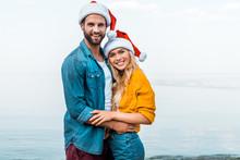 Smiling Couple In Santa Hats Hugging On Beach And Looking At Camera