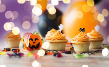 Food, Baking And Holidays Concept - Cupcakes Or Frosted Muffins With Halloween Party Decorations And Candies On Wooden Table