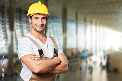 Young builder in hardhat on blurred construction