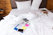 Colorful book on tangle white bed in bed room.busy time,wake up late.
