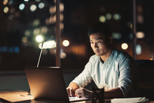 Asian Businessman Using A Laptop At His Desk At Night