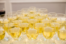 Triangular Row Of Champagne Glasses Stands On A Table With A White Tablecloth