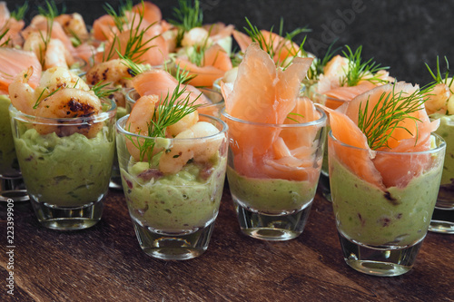 cold buffet with appetizers in glasses, prawn shrimps and salmon on avocado cream and dill garnish on dark wood