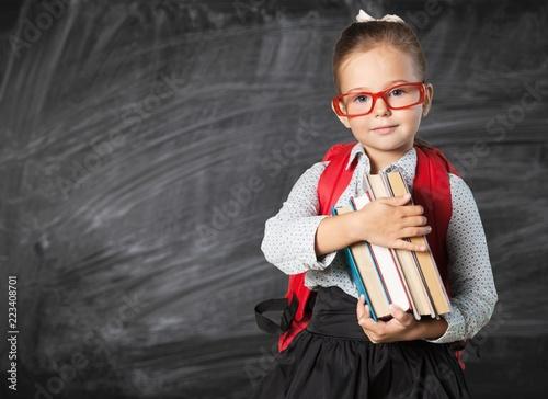 Foto op Canvas Hoogte schaal Cute little schoolgirl in glasses on blackboard