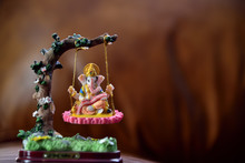 Hindu God-Ganesha In Art Form Sitting On A Swing. Hindu Lord Ganesha Provide Success, Prosperity And Remover Trouble.
