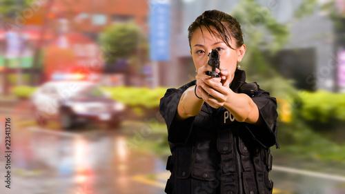 Obraz na płótnie Asian American Woman Police Officer Pointing pistol