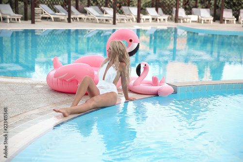 Fotografie, Obraz  Beautiful sexy amazing young woman in white bikini, resting by swimming pool sits near inflatable pink flamingo and tanned, perfect body
