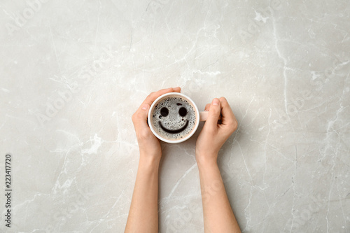 Obraz na plátně  Young woman with cup of delicious hot coffee on light background, top view