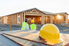 Male And Female Construction Workers At New Home Site