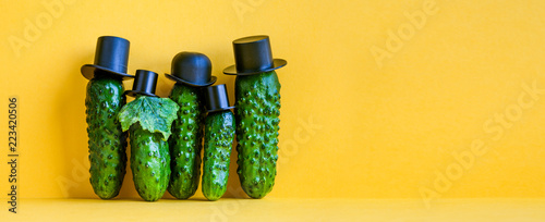 Valokuva  Comical green Cucumbers family on yellow background