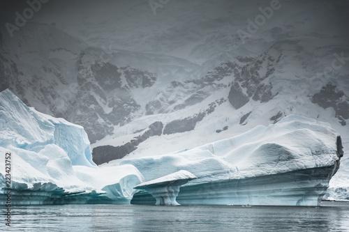 In de dag Antarctica Iceberg against coastline, Paradise Bay, Antarctica