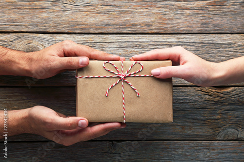 Fotografie, Obraz  Female hands holding gift box with rope on wooden table