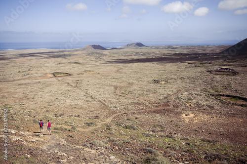 Couple hiking in volcanic landscape descending Calderon Hondo, Fuerteventura, Canary Islands, Spain