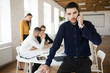 Young business man with beard in dark shirt thoughtfully looking aside while talking on cellphone in office with colleagues on background