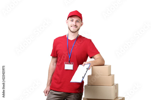 Fotografía  Delivery man with cardboard boxes and clipboard on white background