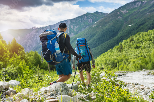 Fototapeta Trekking in mountains. Mountain hiking. Tourists with backpacks hike on rocky way near river. Wild nature with beautiful views. Sport tourism in Svaneti, Georgia. Hikers and climbers in mounts. obraz