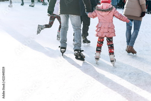 People ride on the skating rink on the ice rink during the Christmas holidays Wallpaper Mural