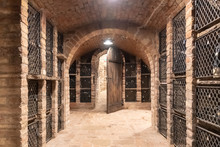 Old Wine Cellar With Wine Storage Cases And Open Vintage Wooden Doors.