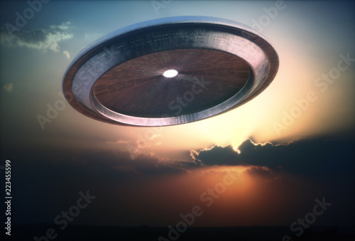 Alien ship UFO arriving on Planet Earth with the sunset in the background.