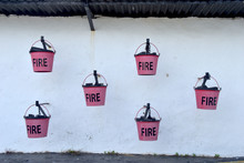 Red Fire Fighting Extinguisher Buckets Ready For Emergencies Attached To White Wall With Black Text