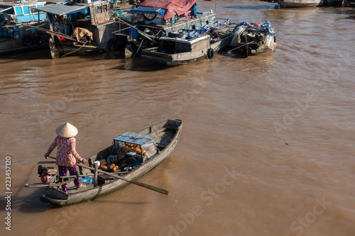 Fotografia  Tourists, people buy and sell food, vegetable, fruits on vessel, boat, ship in Cai Rang floating market, Mekong River
