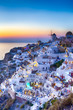 Traveling Concepts. Panoramic View of Famous Old Town of Oia or Ia at Santorini Island in Greece. Taken During Blue Hour with Traditional White Houses and Windmills.