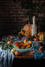 Autumn Still Life: Roasted Pumpkin, Apples, Two Glasses Of Wine, Candles And Fresh Organic Raw Pumpkins On A Wooden Rustic Table. Dark And Moody. Copy Space