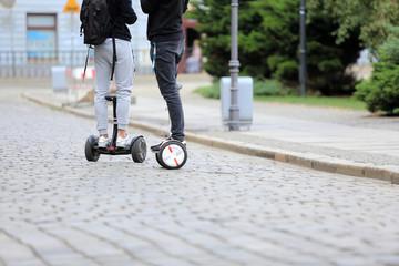 Młodzi ludzie na deskorolkach elektrycznych jadą ulicami miasta Wrocław, hoverboard.