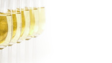 Glasses Of Champagne Lined Up. For New Years Eve Celebration And Special Moments. Empty Copy Space For Text On Simple White Background.