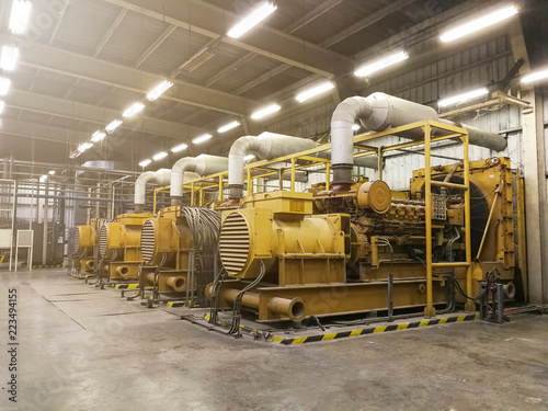 Fotografiet A very large electric diesel generator in factory for emergency,equipment plant