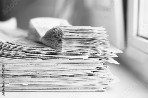 Fotografía  Stack of newspapers and bundle of money, side view
